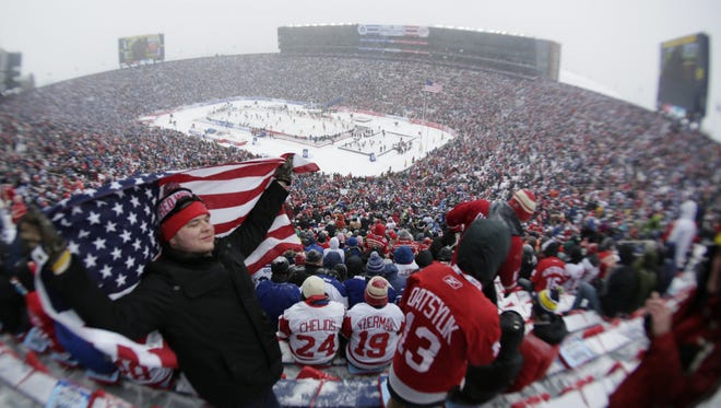 Nate Hamel, 21, of Big Rapids poses for a photo as he wraps himself in the American flag before the 2014 Bridgestone NHL Winter Classic at Michigan Stadium in Ann Arbor Wed. Jan. 1, 2014.