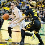 Iowa's Samantha Logic dribbles around Minnesota's Carlie Wagner (33) during the first half at Carver-Hawkeye Arena on Sunday. Logic averaged 22 points, 11 assists and eight rebounds in two wins last week.