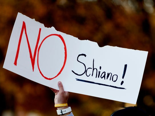 "A fan holds a sign reading ""No Schiano!"" during a gathering"