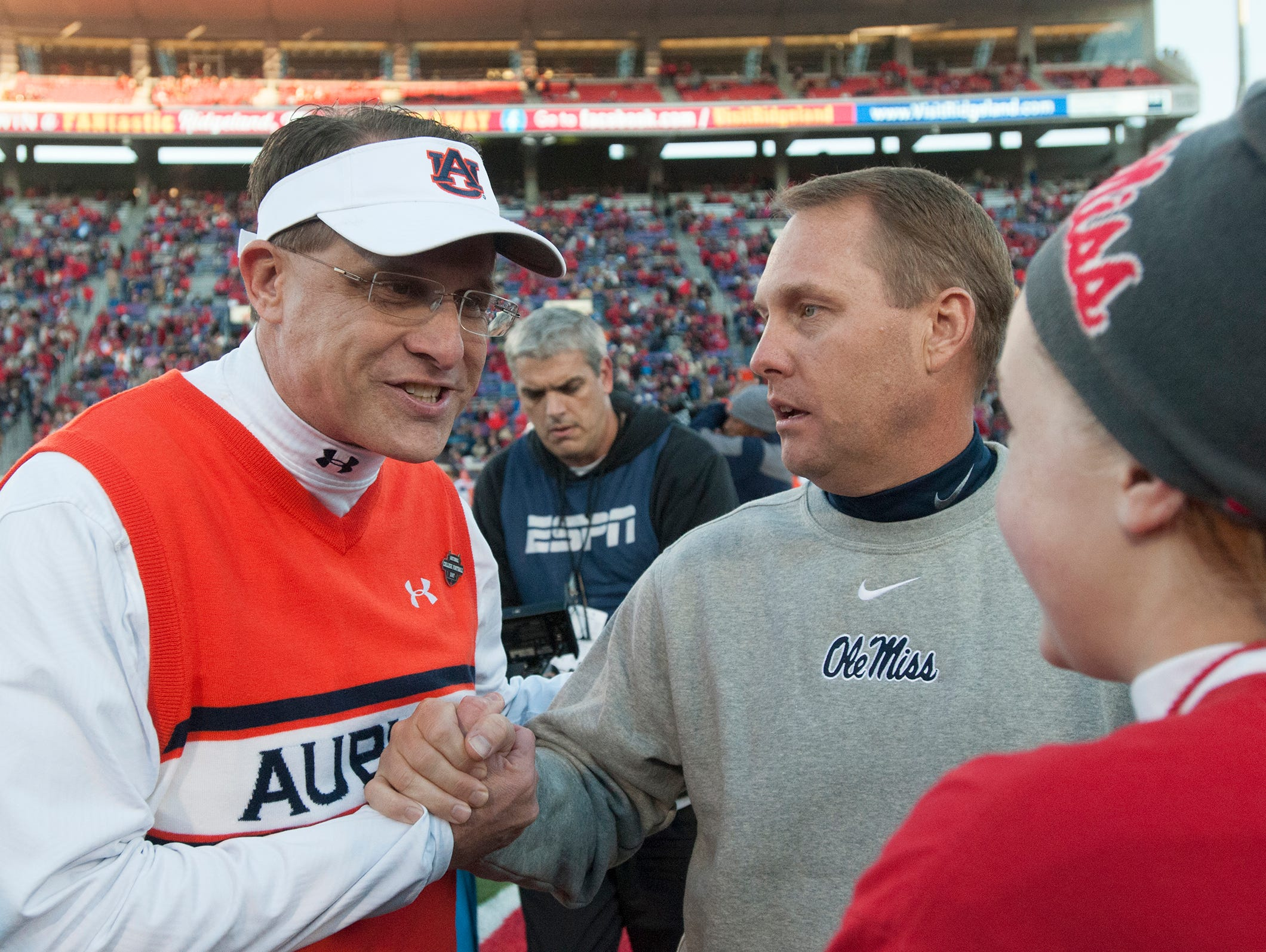 Auburn coach Gus Malzahn shakes Mississippi coach Hugh Freeze's hand as he says buy to Freeze's daughter, Reagan Freeze, before the NCAA football at University of Mississippi in Oxford, Miss., on Saturday, Nov. 1, 2014.