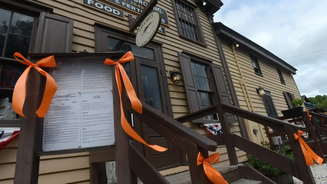 Orange ribbons adorn the steps of Mallards at the Wharf in the historic Hopkins Bros. store at the Onancock Wharf. The ribbons have been placed around Onancock in preparation for the 10th annual Music for the Hungry benefit concert.