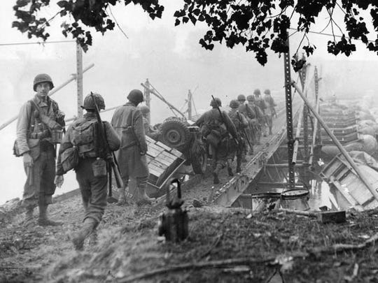 Felix Longoria looks back while his platoon crosses the Moselle River into Germany during World War II.