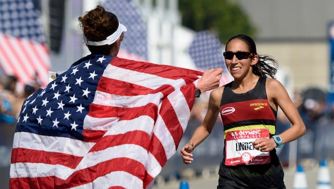 Amy Cragg, left, celebrates with Desiree Linden, right, as she crosses the finish line during the U.S. Olympic marathon trials, Saturday, Feb. 13, 2016, in Los Angeles.