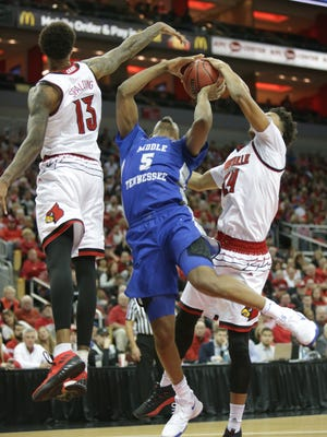 Ray Spalding and Dwayne Sutton block a shot by Nick King of Middle Tennessee State.
