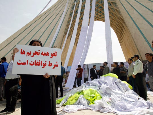 An Iranian demonstrator holds a placard reading in