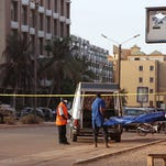 A body is carried near the Splendid Hotel, left, where suspected militants attacked in Ouagadougou,  Burkina Faso, Saturday, Jan. 16, 2016.