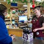 Tristan Raitan buys Left Hand Milk Stout from Katie Karo at Wilbur's Total Beverage in Fort Collins on March 7.