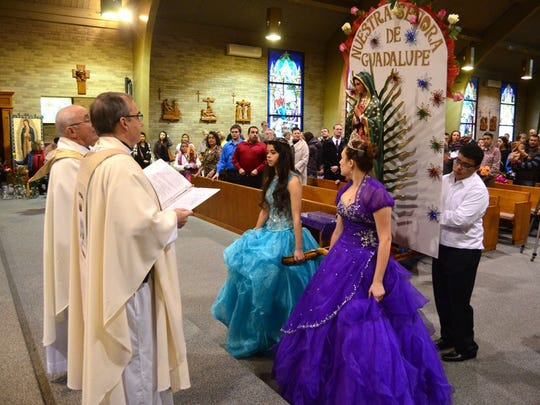 Corpus Christi pastor Father Carl Schmitt, right, with senior priest Father Tony Birdsall, gives a greeting and a blessing as the statue of Our Lady of Guadalupe arrives at the church on Dec. 13. Juanita Sandoval (left, turquoise) and Selena Rose Reyes, who recently celebrated their quinceanera feast, helped carry the litter down the aisle.
