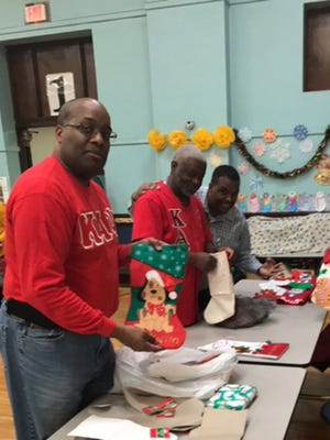 Kappa men Craig Smith, left to right, Wesley Lee, David Scott and Cameron Smith help stuff stockings during the Dec. 20 community Christmas party.