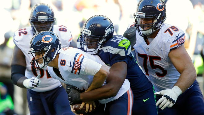 FILE - In this Sept. 27, 2015, file photo, Seattle Seahawks defensive end Cliff Avril (56) tackles Chicago Bears quarterback Jimmy Clausen (8) as Bears' Kyle Long (75) looks on in the second half of an NFL football game in Seattle. Avril landed in Seattle because of what he accomplished during his first five seasons spent in Detroit. Now he faces the Lions as an opponent for the first time on Monday night.  (AP Photo/Elaine Thompson, File)