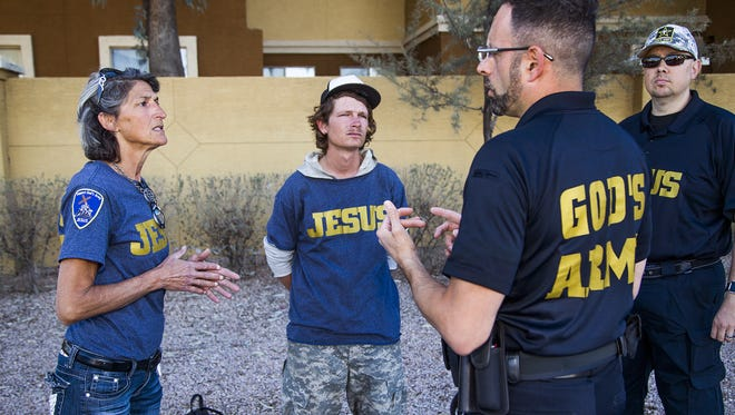 Georgia Watson, left, and Tyler Richards listen to Richard Tamayo of God's Army, third from left, in a parking lot in north Phoenix on March 1, 2018.