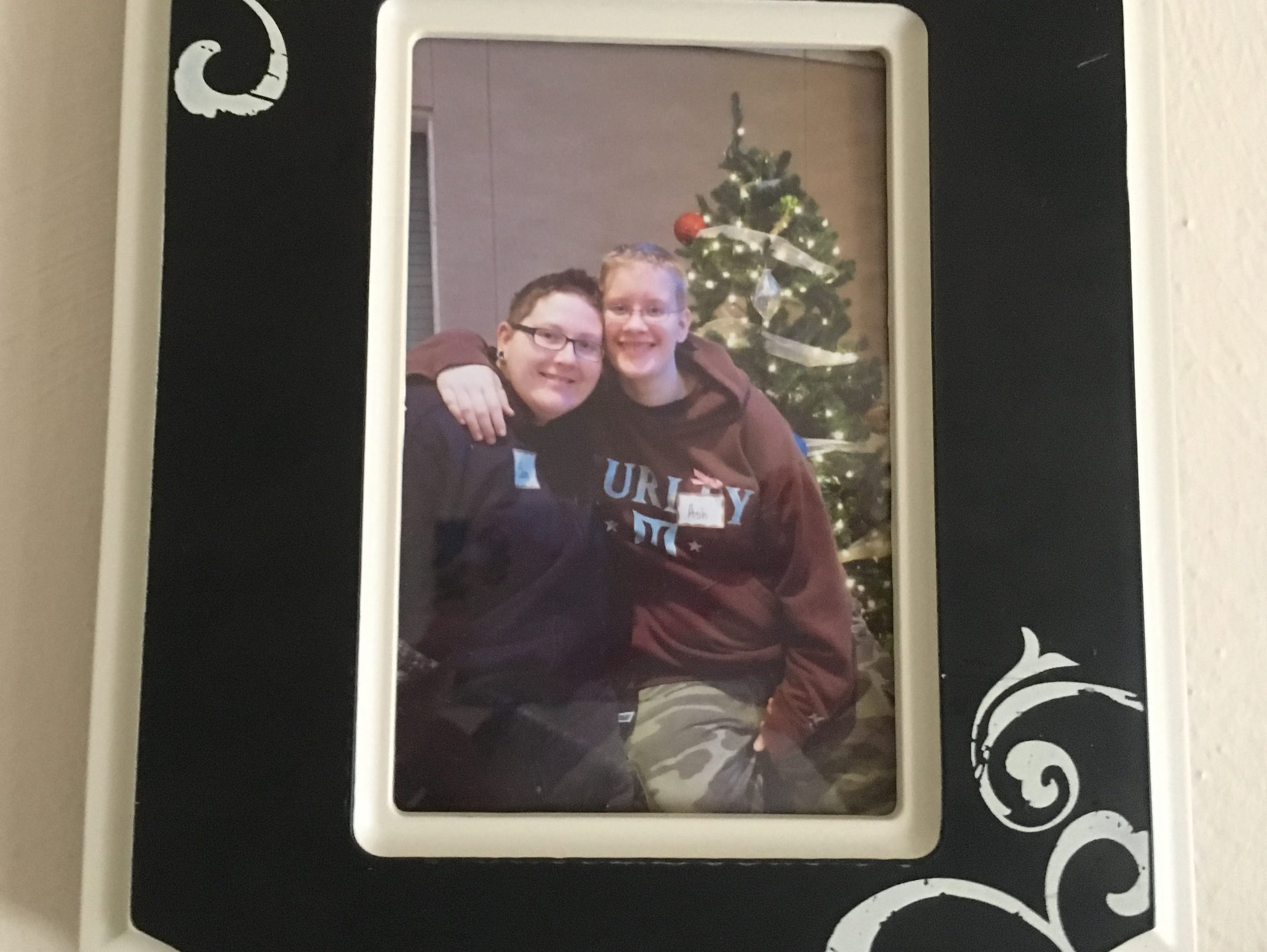A Christmas picture of the couple hangs on a wall at