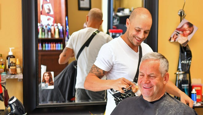 Talking about the future of Puerto Rico. Stephen Soto, a father of three whose parents were born in Puerto Rico, and who visits their often. He owns Friss Hair Lounge, a full service salon and barber shop in West Melbourne. The customer is Bob DiBella.