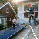 Jacob Bruce, 20, carries a solar panel for the roof of Tom Cunningham and Lorraine Venberg off Brownsboro Rd.  August 27, 2015