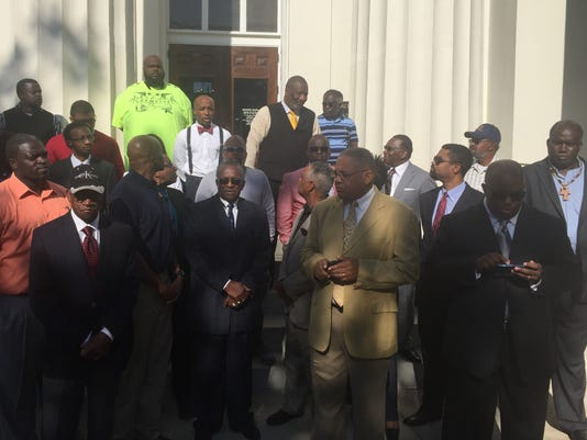 African-American ministers and business owners gather outside City Hall