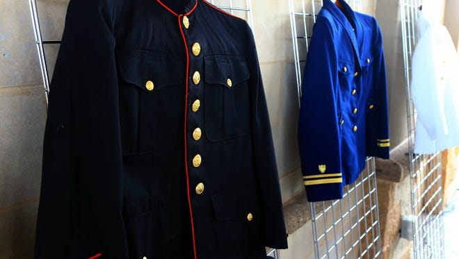 Military dress uniforms donated to Uniforms for the Final Salute are displayed during a news conference.