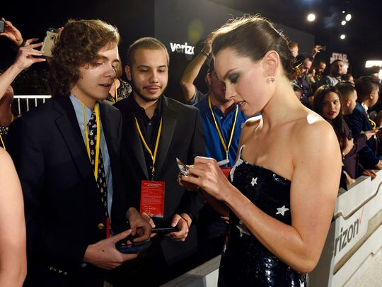 "Daisy Ridley, right, a cast member in the film ""Star Wars: The Last Jedi,"" signs an autograph as Tyler Woodward, 17, left, and Chris Alegria, 18, look on at the premiere of the film at the Shrine Auditorium in Los Angeles on Dec. 9.  Woodward and Alegria were two of seven teens with life-threatening medical conditions who were among the special guests at the premiere as part of the Make-A-Wish Foundation."