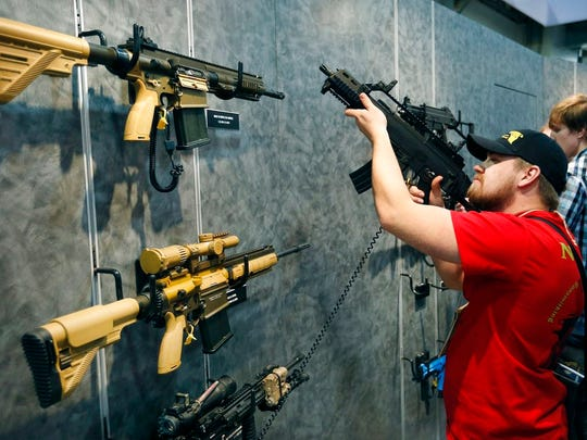 In this Jan. 19, 2016 file photo, Nolan Hammer looks at a gun at the Heckler & Koch booth at the Shooting, Hunting and Outdoor Trade Show in Las Vegas.