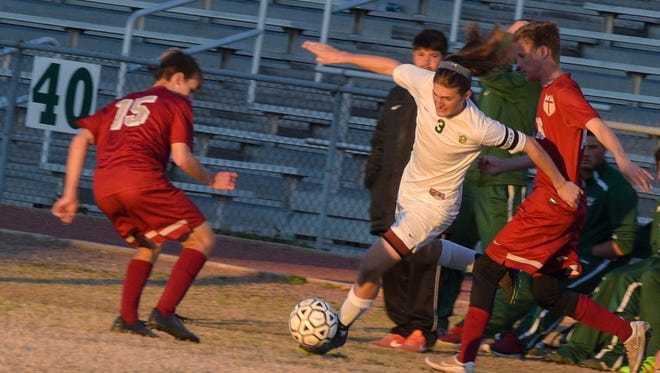 Bailey Deroussel fights off two defenders to move the ball as Acadiana High Boys Soccer takes on Brother Martin High School.