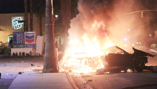 Burning wreckage of the chased vehicle involved in a fatal high speed pursuit that killed Cathedral City officer Jermaine Gibson, and injured two others in Palm Springs, late Friday, March 18, 2011.