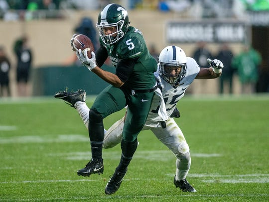 Michigan State's Hunter Rison, left, catches a pass
