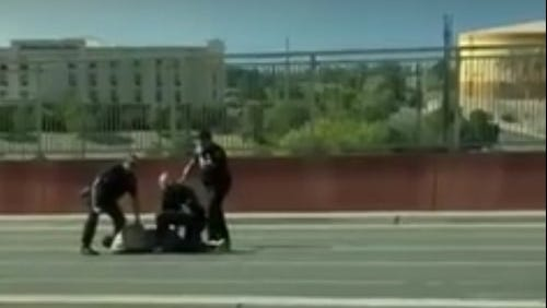 In this still from a video posted to Facebook, three Las Cruces Police Department officers surround a man after he was shot by police on the Lohman Avenue bridge over Interstate 25 on Sunday, Aug. 21, 2016.