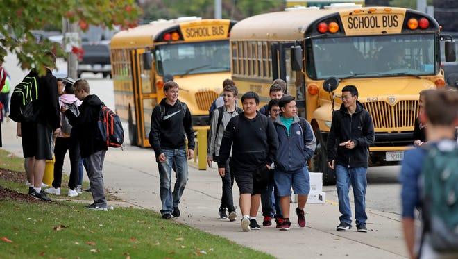 Students board buses to depart Green Bay Preble High School.
