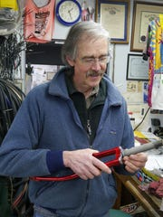 Owner Michael Wolfe repairs a bicycle fork.