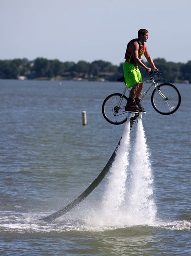 While balancing a bike on a flyboard, Jeff Luft of Storm Lake greets cyclists in Storm Lake during RAGBRAI, Sunday, July 19, 2015.