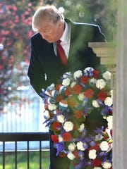 President Donald Trump lays a wreath on the grave of