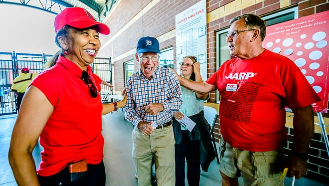 Eric Schneidewind, center, the newly elected president of the AARP Board of Directors, shares a laugh with AARP state director Paula Cunningham, left, and AARP volunteer James Blair, right, Tuesday June 14, 2016 at AARP Night during the Lugnuts/Great Lakes Loons game at Cooley Law School Stadium in Lansing.