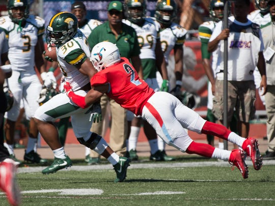Delaware State's Jahad Niebauer (2) makes a sideline tackle on Norfolk State's Aaron Savage (30) in their 7-17 loss against Norfolk State University.