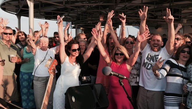 Glass Onion fans, including Carmen Natrin, dance during a Glass Onion performance aboard the Cape May-Lewes Ferry.