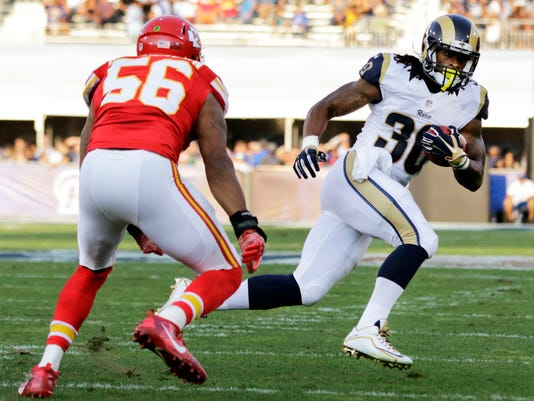 FILE - In this Aug. 20, 2016 file photo, Los Angeles Rams running back Todd Gurley, right, runs the ball while under pressure from Kansas City Chiefs inside linebacker Derrick Johnson, left, during the first half of a preseason NFL football game against in Los Angeles.  With Case Keenum and Blaine Gabbert set as starting quarterbacks, Colin Kaepernick's refusal to stand for the anthem getting more public acceptance and the Rams mostly settled into their new home, much of the focus when the teams open the season on Monday night will be on the running backs.(AP Photo/Ryan Kang, File)