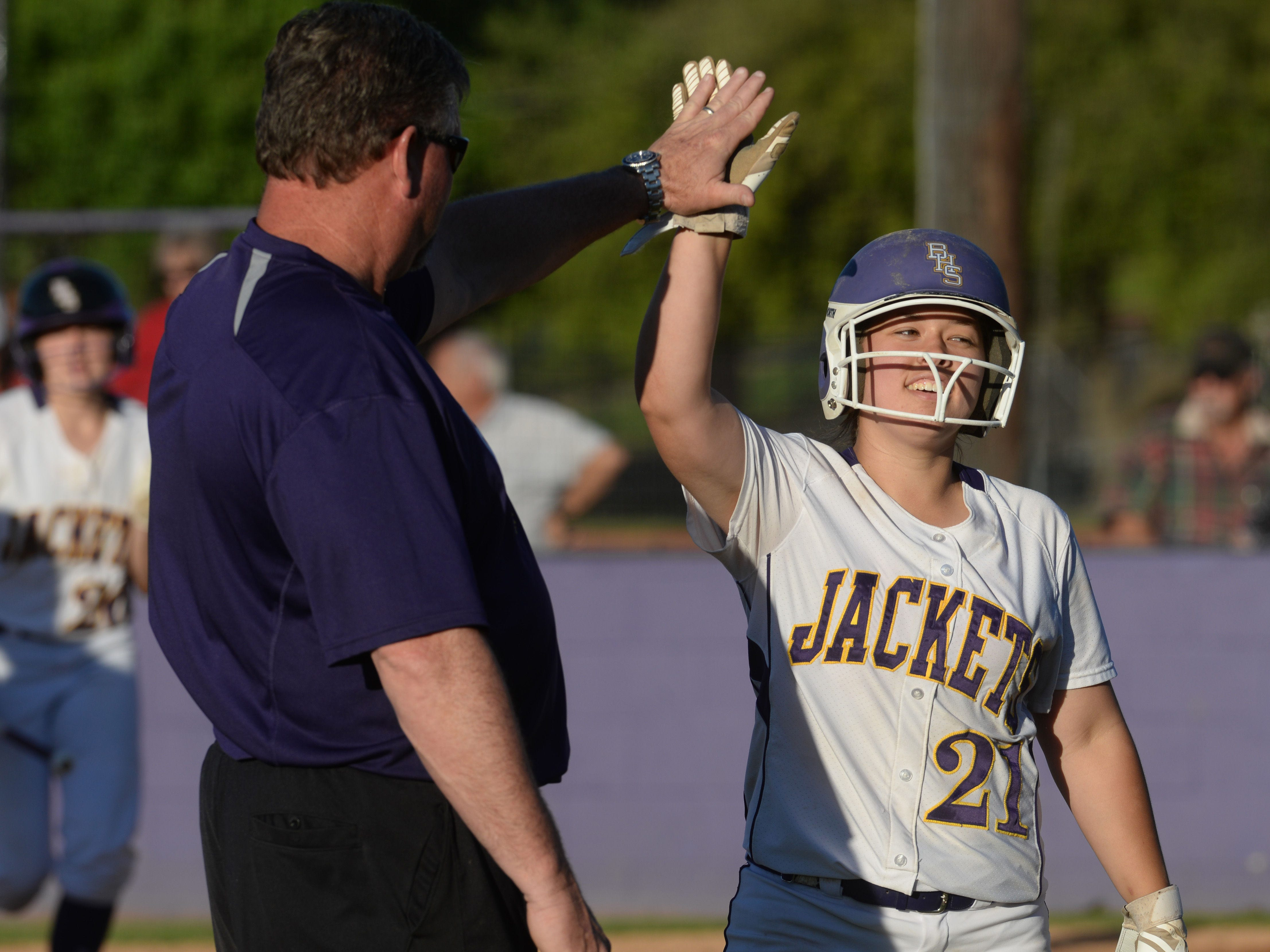 Byrd's Alex Wynne is high-fived by coach Mark Lambert after her 2-run double in the sixth inning against Haughton.