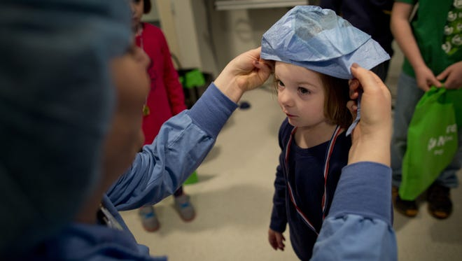 Registered nurse Jessica Kaslik puts a surgical cap on Finley Badley, of Marysville during the 2015 Children's Fun and Fitness Festival at McLaren Port Huron.