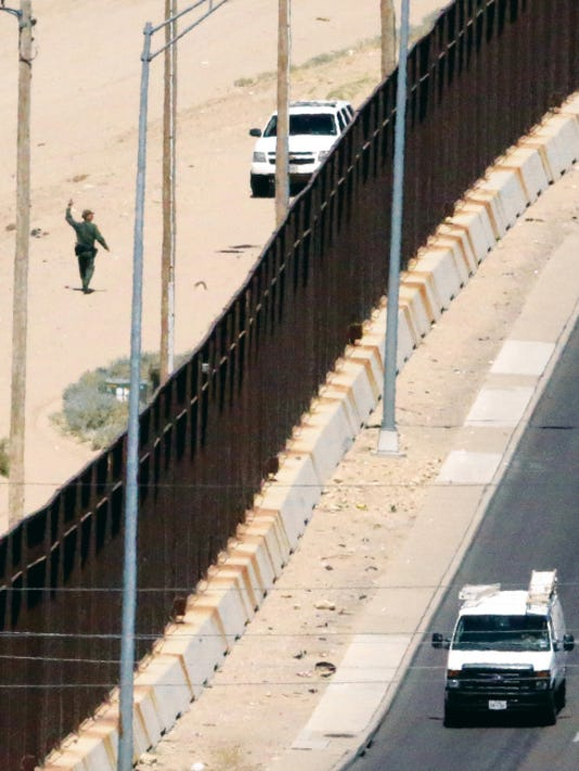 A U.S. Border Patrol agent at left raises his arm in the air, signaling to someone else, while appearing to search for a possible illegal border-crosser near the Rio Grande River levee along West Paisano Drive on Friday. The local Border Patrol union is saying new policies and criticisms are causing problems.