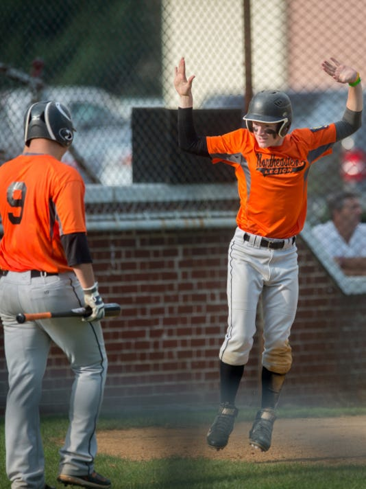 Northeastern's Jonah Latshaw, center, celebrates after a pop-up slide through home plate as Adam Kipp (9) waits to bat during the York-Adams American Legion baseball championship game in Manchester on July 13. Northeastern defeated Pleasureville, 5-0.