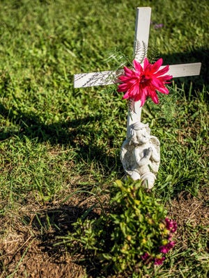 An angel figurine and cross mark the grave of Cody Laughman at a cemetery in Biglerville.