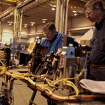 Steve Corbat, left, from Fraser and John Schuler from Saline inspect components before they are placed into a weld cell on Dec. 12 at The Paslin Company in Warren. Michigan's jobless rate now matches the national average for the first timne in 15 years.