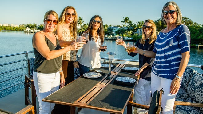 Guests Donna Lewis, Vivien Bunce, Alex Cotleur, Norma Huempfner, and Vicki Pfeil enjoy a glass of wine as they prepare for a sunset dinner cruise