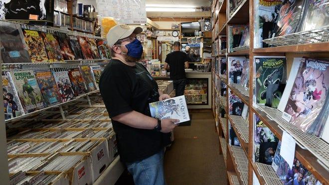Brent Ahlgren of Jamestown, New York, shops for comic books at Books Galore in Millcreek Township on Aug. 15.