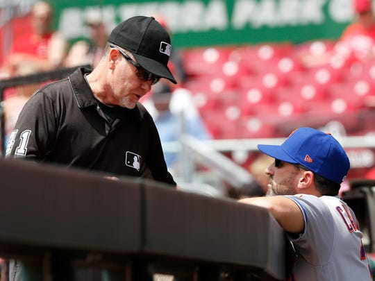 Third base umpire Jerry Meals (left) talks with New