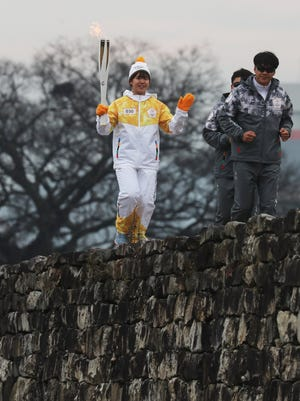 Lee Ha-young, a weightlifter, carries the torch for the 2018 PyeongChang Winter Olympics at a fortress in the southwestern town of Namwon, South Korea, on Nov. 28, 2017.