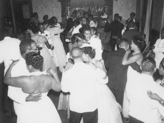 Couples crowd the dance floor inside the building at Montgomery Hall Park.