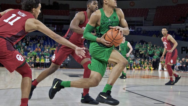 Oregon guard Elijah Brown (right) dribbles past Oklahoma guard Christian James (center) and guard Trae Young (left) during the second half of an NCAA college basketball game in the Phil Knight Invitational tournament in Portland on Sunday, Nov. 26.