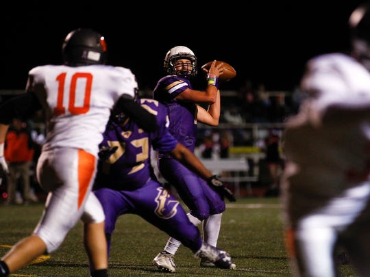 Kirtland Central quarterback Bryson Dowdy searches for a receiver during Friday's game against Aztec at Bronco Stadium in Kirtland.
