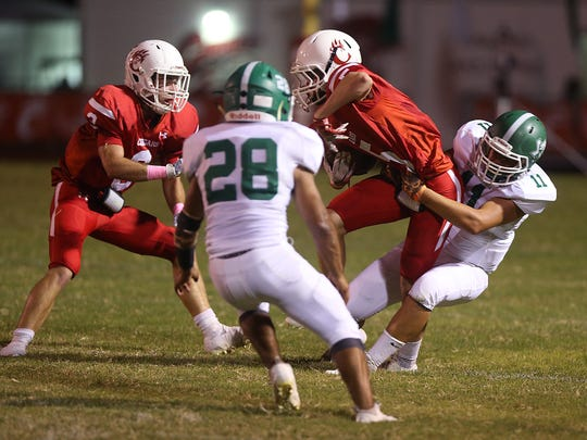 Eldorado Eagle Cesar Garcia (#11) tackles Chrostoval Cougar Lance Young (#5) during Friday night's game in Christoval, Oct. 13, 2017.
