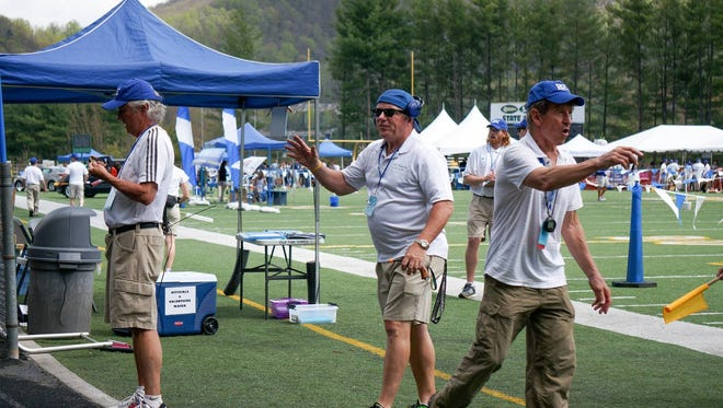 Bill Abromitis, middle, works the finish area of Saturday's Blue Ridge Classic track meet at Reynolds.