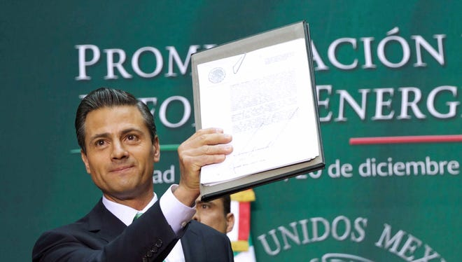 Handout picture released by the Mexican Presidency press office of Mexican President Enrique Pena Nieto showing the signed decree to promulgate the energy reform, during a ceremony at the National Palace in Mexico City, on December 20, 2013. Pena Nieto signed on December 20, 2013 a controversial law opening the country's oil industry to foreign investment for the first time since it was nationalized in 1938, after a majority of Mexican states voted to ratify it.